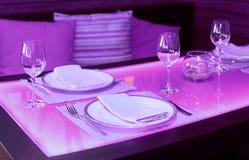 与橙色背后照明的玻璃餐桌 免版税库存照片