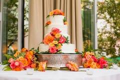 与橙色花的白色婚宴喜饼 免版税库存照片
