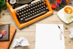 与橙色葡萄酒打字机的工作区有白色空白的 夏天领域花束开花和杯子甘菊茶 图库摄影
