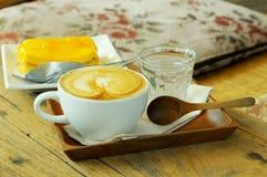 与橙色蛋糕的咖啡具在木桌上 免版税库存图片