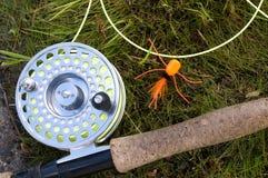 与橙色蜘蛛诱饵的用假蝇钓鱼标尺在草 免版税库存照片