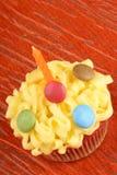 与橙色蜡烛的花梢生日杯形蛋糕 库存图片