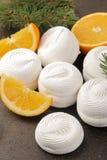 与橙色装填和新鲜的桔子的甜白色蛋白软糖和圣诞树小树枝在黑暗的背景甜点的 点心 免版税库存照片