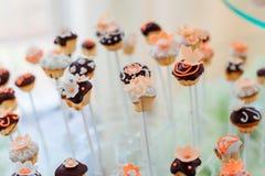 与橙色釉花架的被烘烤的甜点在棍子 免版税库存图片