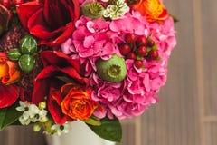 与橙色,绯红色和红葡萄酒玫瑰、鸦片和其他花和绿色的土气婚礼花束在木背景 免版税库存照片