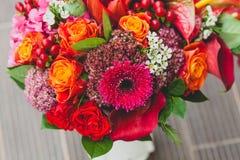 与橙色,绯红色和红葡萄酒玫瑰、鸦片和其他花和绿色的土气婚礼花束在木背景 库存图片