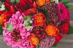 与橙色,绯红色和红葡萄酒玫瑰、鸦片和其他花和绿色的土气婚礼花束在木背景 免版税图库摄影