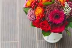 与橙色,绯红色和红葡萄酒玫瑰、鸦片和其他花和绿色的土气婚礼花束在被弄脏的木 免版税库存照片