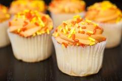 与橙色结冰的杯形蛋糕 免版税库存照片