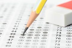 与橡皮擦和铅笔的被填装的答案纸 免版税图库摄影