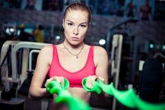 与橡皮筋儿的严肃的少妇锻炼在健身健身房 免版税库存照片