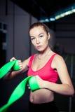 与橡皮筋儿的迷人的少妇锻炼在健身健身房 免版税库存照片