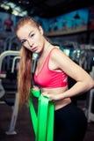 与橡皮筋儿的迷人的少妇锻炼在健身健身房 免版税库存图片