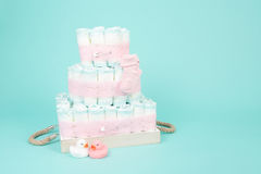 与橡胶鸭子和桃红色袜子的尿布蛋糕在蓝色背景 免版税图库摄影