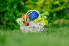 与欢乐复活节礼物、多色的鸡蛋和玩具的篮子 图库摄影