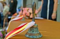 与欢乐色的丝带的古铜色减速火箭的校铃 免版税库存照片