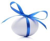 与欢乐蓝色弓的复活节彩蛋在白色背景 库存图片