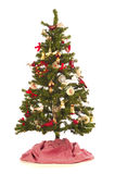 与欢乐装饰的圣诞树,古色古香和新,在与一条红色和白色树裙子的白色背景 图库摄影
