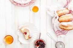 与欢乐sufganiyot油炸圈饼的茶时间用果冻填装了 免版税库存图片