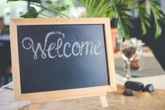与欢迎消息的黑板标志在咖啡店 免版税库存图片