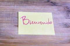 与欢迎消息的黄色笔记用西班牙语- bienvenido 免版税库存图片