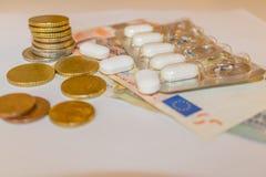 与欧元钞票和硬币的白色Tabletts 概念Pharmaceu 免版税图库摄影