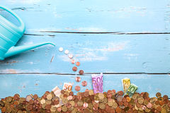 与欧洲硬币和钞票的喷壶在蓝色背景, c 库存图片