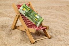 与欧洲钞票的海滩睡椅 免版税库存图片