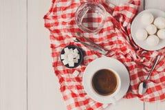 与款待的早晨咖啡在wh的时髦的方格的桌布 库存照片