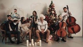 与歌手的串五部合唱开始使用在有圣诞节风景的屋子里 影视素材