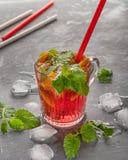 与止您的干渴的冰和鸡尾酒管橙色切片和片断的轻的碳酸化合的樱桃饮料在一热的天 免版税库存照片