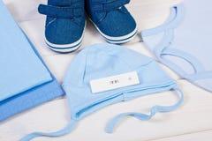 与正面结果的新出生的妊娠试验和衣物,期望为婴孩概念 免版税库存图片