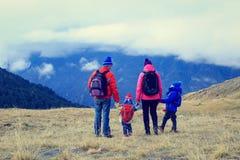 与步行在冬天山的两个孩子的家庭 库存照片