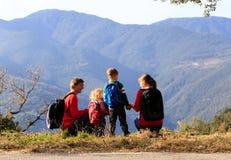与步行在山的两个孩子的家庭 库存照片