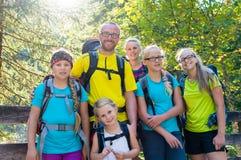 与步行在山的四个孩子的家庭 库存图片
