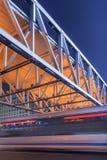 与步行桥和公共汽车的夜场面在行动迷离,北京,中国 免版税图库摄影