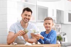 与残破的存钱罐和金钱的家庭 图库摄影