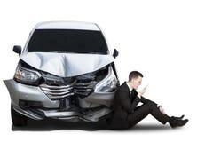 与残破的汽车的恼怒的商人 免版税库存图片
