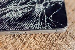 与残破的玻璃的智能手机显示在wodden桌上 免版税库存照片