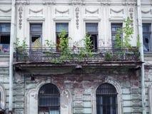 与残破的窗口和一个被破坏的阳台的美丽的老被放弃的大厦 免版税库存图片