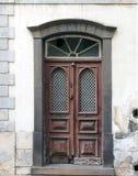 与残破的被修理的盘区的老华丽棕色双重房子门和与石框架和门阶的手形状的敲门人 免版税库存图片