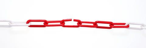 与残破的元素的红色链子在白色 免版税库存照片