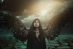 与残破的翼的黑暗的天使 免版税库存图片