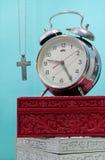 与残破的闹钟,与金属neckl的金属十字架的静物画 免版税图库摄影