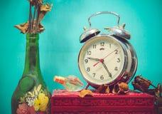 与残破的闹钟,有死的ros的老玻璃花瓶的静物画 库存图片