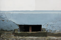 与残破的玻璃的窗口在一间地下室在一个老房子毁坏了灰泥灰色和灰棕色 库存图片