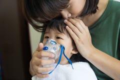 与母亲的亚洲女婴呼吸的治疗保重,在ro 图库摄影