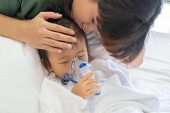 与母亲的亚洲女婴呼吸的治疗保重,在ro 免版税库存照片