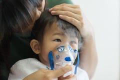 与母亲的亚洲女婴呼吸的治疗保重,在ro 免版税图库摄影