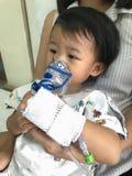 与母亲的亚洲女婴呼吸的治疗保重 免版税库存照片